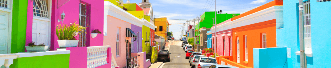 An image of a street in Bo Kaap, Cape Town, showing the neighbourhood's brightly coloured houses on either side.