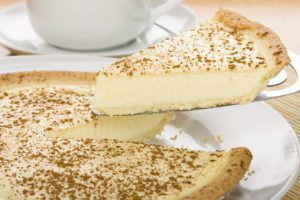 A slice of milk tart (traditional South African dessert)with coffee or tea cup in the background.