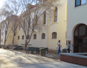 Two female students stand in conversation in front of the Hiddingh Library building