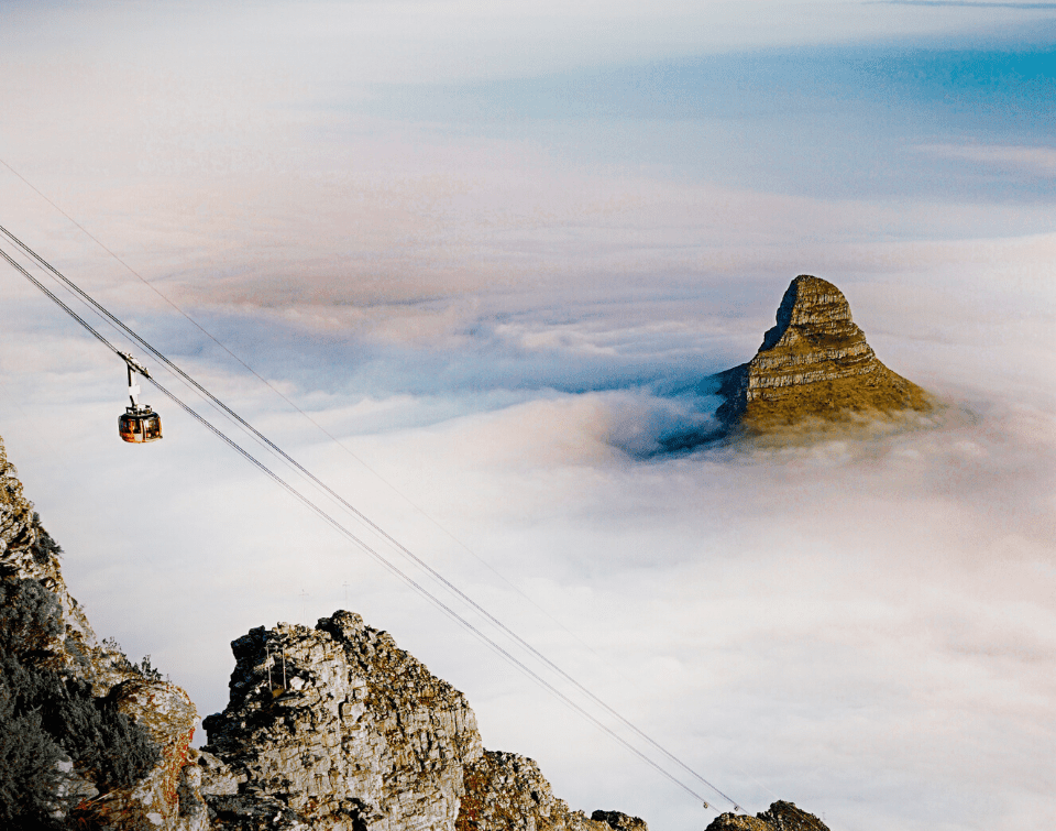 The cable car ascends Table Mountain, with Lion's Head in the background