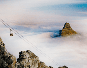The cable car ascends Table Mountain with Lion's Head seen in the background