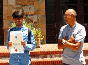 Teacher smiles proudly as student receives certificate
