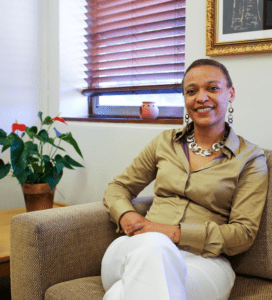 Dr. Shose Kessi -Dean of the Humanities Faculty at the University of Cape Town - sits on a couch in their office