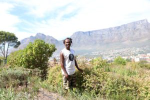 Portrait of Unathi Dyanti at his permacultre garden with Table Mountain in the background
