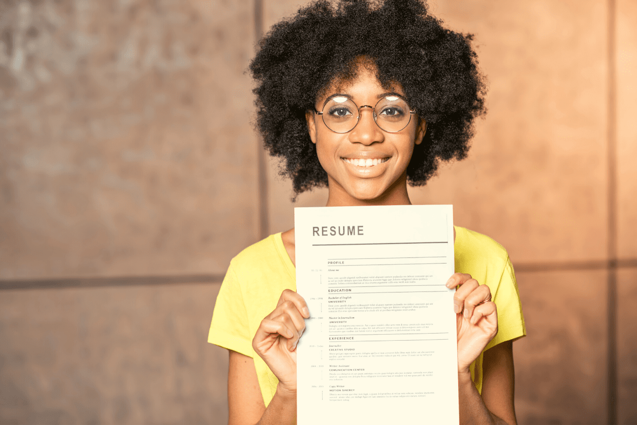 A smiling person holding their resume