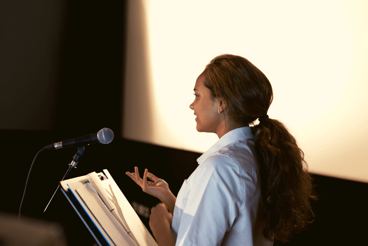 A woman stands at a podium delivering a presentation
