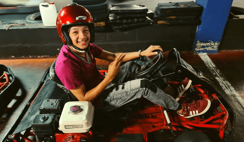 A smiling person sits in a go karting