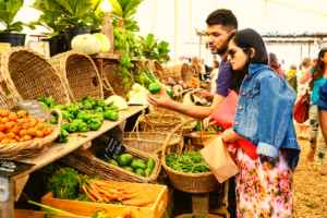 Two people shop for produce at the Oranjezicht Farm Market