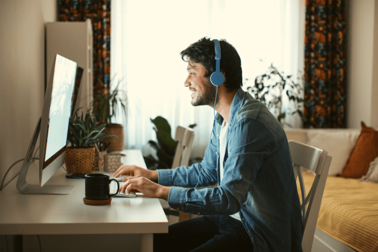 Smiling student with a headset on in front of a PC