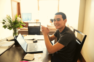 Smiling young man in front of a laptop with someone watching TV in the background