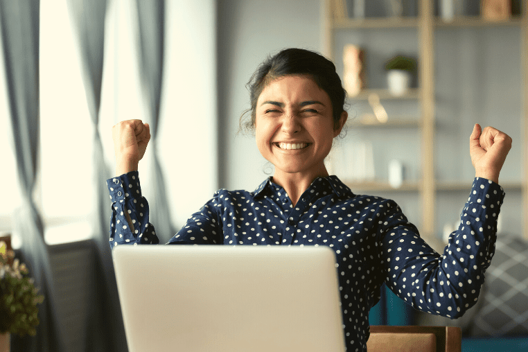 Smiling student with fists held triumphantly in the air in front of a laptop