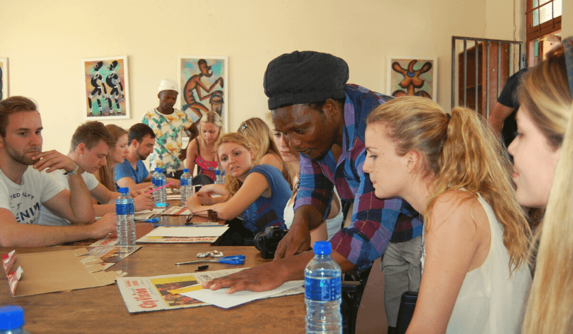 Mzi demonstrates work to a group of students seated around a table