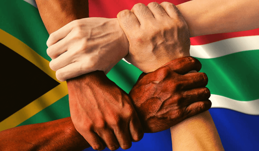 Four hands holding each other's wrists with the South African flag in the background