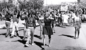 A crowd of young people march through a street in Soweto in 1976