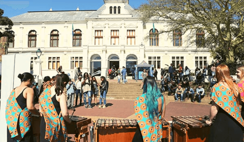 A group of women play marimba with the Iziko Museum in the background