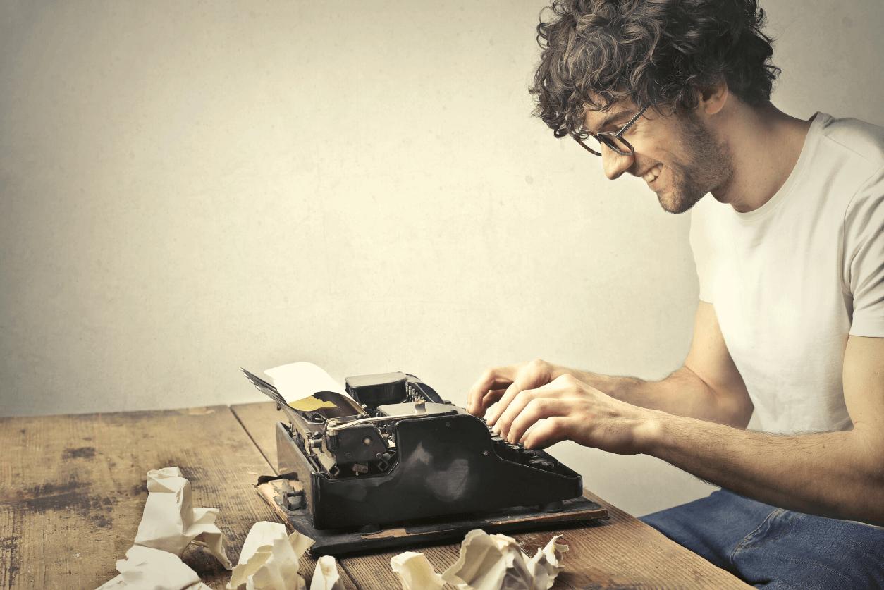 Smiling writer types on a typewriter