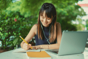A smiling student makes notes while seated in front of a laptop with a garden in the background