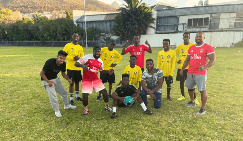 A group of students stand on a soccer pitch