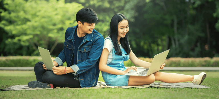 Two students working on their laptop in a park